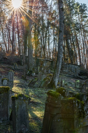 Sun beams at old Jewish cemetery with weathered tombstones, Germany