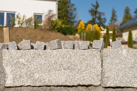 Granite wall and many small granite stones for road coating Stock Photo