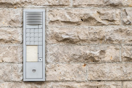 Worn doorbell with intercom on a house wall