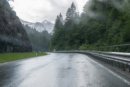 Rainy road surface and raindrops on a car windshield