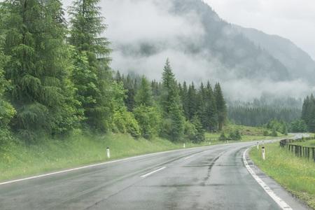 Regnerische Straßenoberfläche und Regentropfen auf einer Autowindschutzscheibe