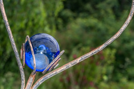 Heart-shaped garden plug decorated with a blue glass ball