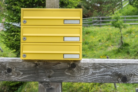 Yellow letterbox made of tin without a name in a rural area, Austria Archivio Fotografico