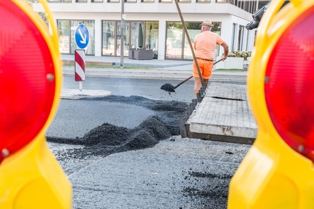 Road workers distributing the hot asphalt with shovels on the road, Germany