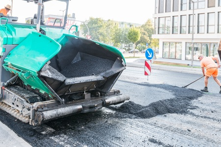 Close-up of an asphalt paver on a construction site renewing the road surface, Germany Stock Photo