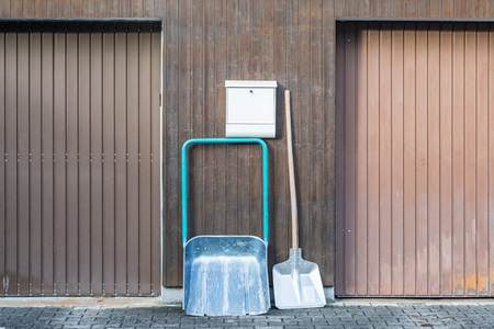 Snow shovel in front of a double garage without snow, Germany Imagens