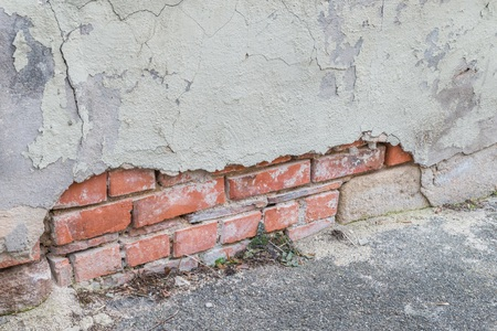 Un muro di casa danneggiato e un esterno scheggiato con un grande foro, Germania