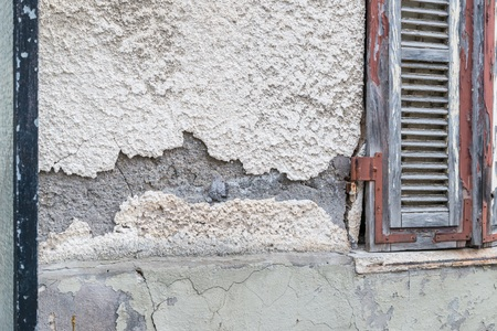 A damaged house wall and flaked exterior with a large hole, Germany