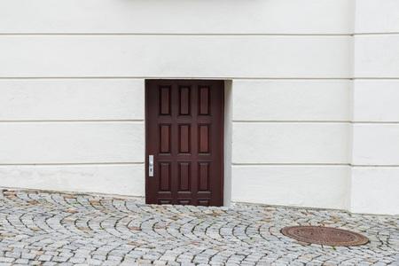Curious wooden front door sunk in the street, Germany Foto de archivo - 120562736