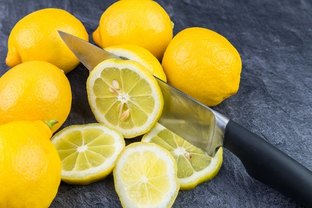 A sharp kitchen knife cuts a lemon into slices