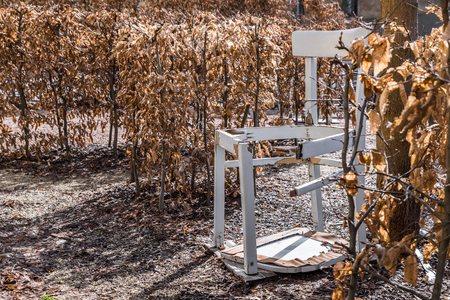 A broken white chair in a garden Labyrinth, Germany