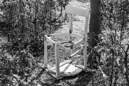Black white image of a broken white chair in a garden Labyrinth, Germany