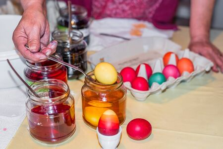 Old woman dyeing Easter eggs at home in the kitchen in the cucumber glass and with different colors, Germany 写真素材