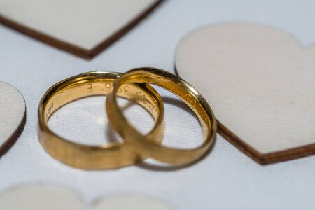 Golden wedding rings on a table with hearts of wood, Germany