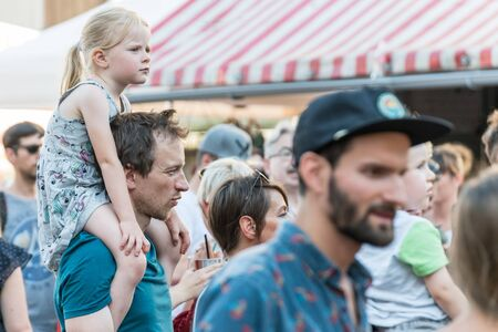 Regensburg, Bavaria, Germany, June 28, 2019, Little girl sitting on her fathers shoulders during a live concert at the Buergerfest in Regensburg 2019, Germany