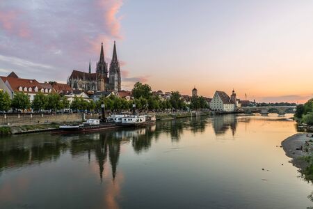 Regensburg during sunset with Danube and cathedral and stone bridge, Germany