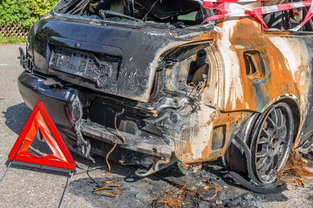 Burnt out car after a severe accident with warning triangle, Germany