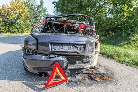 Burnt out car after a violent accident with police barrier tape in red and white with the German word for police barricade, Germany