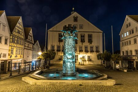 Hechingen, Baden-Württemberg, Germany, September 14, 2019, Night shot of the illuminated fountain on the market place in front of the town hall in Hechingen in Baden-Württemberg, Germany by the sculptor Klaus Ringwald