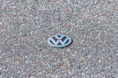 Grafenau, Bayern, Germany, March 15, 2020, VW logo lies on the asphalt of a road with a wilted leaf