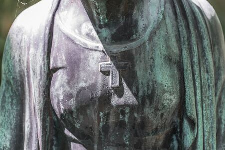 Detail image of a female breast with cross of a bronze statue of a woman in a park, Germany