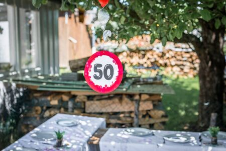Birthday party with tables in a garden under a tree with a paper sign with the number 50 made like the road sign for speed limit, Germany