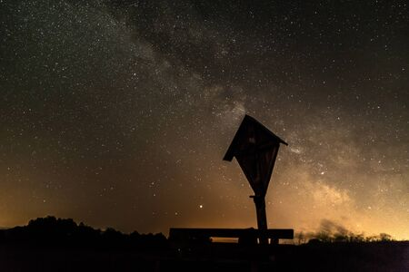 Starry sky with the Milky Way galaxy in summer with a wayside cross and a wooden bench in front of an illuminated city, Germany