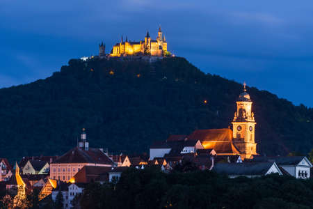 Night shot at the blue hour from the city of Hechingen in the foreground and Hohenzollern Castle in the background, Germany