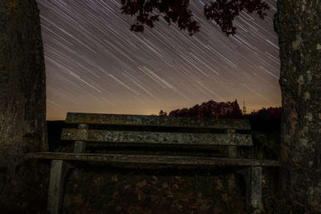 Star trails in a starry night with a wooden bench between two trees, Germany