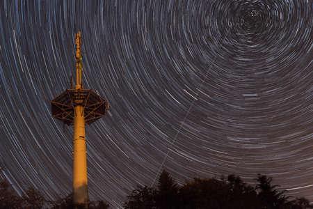 Radio tower near Liebersberg at Grafenau in the Bavarian forest at night with star trails around the Polarstern, Germany 免版税图像 - 157860473