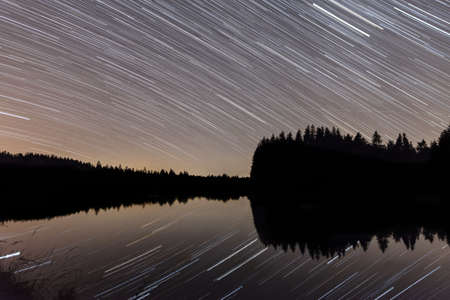 Star trails in a starry night in front of a reservoir with reflections in the lake, Germany