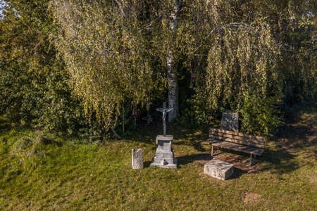 Picture of a wayside cross in front of a big tree with wooden bench in Bavaria, Germany 免版税图像 - 159014796