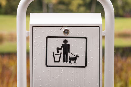Waste garbage can for dog bags that looks like a white metal mailbox in a park by a lake for recreation and walking, Germany
