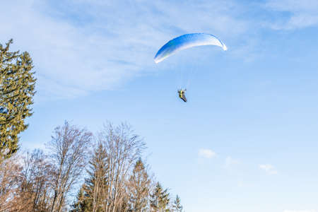 Taking off hobby paraglider pilot on a mountain slope with professional equipment in autumn, Germany
