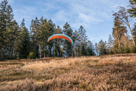 Taking off hobby paraglider pilot on a mountain slope with professional equipment in autumn, Germany Imagens