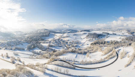 Picture of an aerial view with a drone of the village Grueb near Grafenau in the Bavarian forest with mountains and landscape in winter with snow and ice, Germany