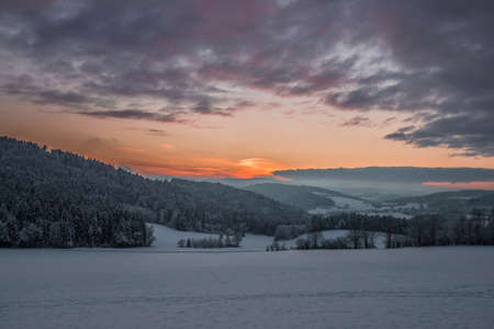 Landscape during sunset in winter with snow and ice and mountains in background near Grafenau in Bavarian Forest with clouds and sun rays, Germany
