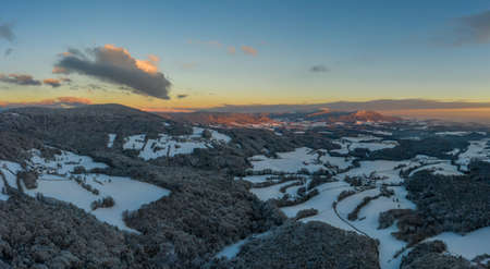 Sunset in winter with snow and ice with view from Rusel towards Schaufling and Landshut, Germany