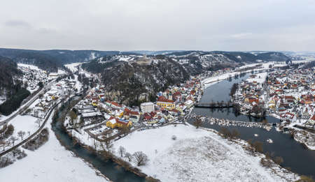 Aerial view from drone of town view of market Kallmünz Kallmuenz in Bavaria and bridge over river Naab and castle ruin in winter with snow and ice, Germany