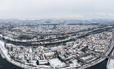 Panorama of Regensburg city in Bavaria with the river Danube the cathedral and the stone bridge in winter with snow and ice, Germany
