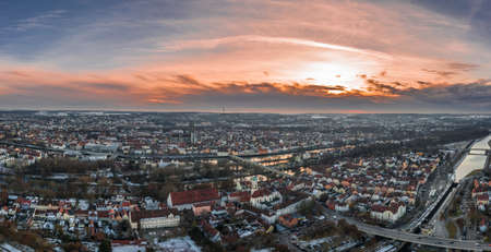 Panorama of Regensburg city in Bavaria with the river Danube the cathedral and the stone bridge in winter with snow and ice during sunset, Germany