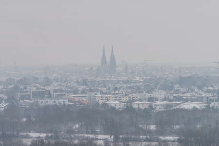 View of the cathedral in Regensburg during a foggy morning in winter with snow and ice, Germany