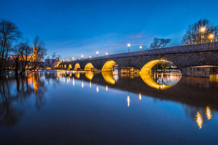 Flood of Danube river in winter 2021 in Regensburg with flooded Jahn Island with view of cathedral and illuminated stone bridge at blue hour, Germany