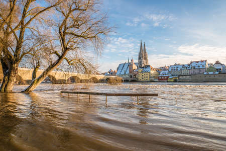 Sunset during flood of Danube river in winter 2021 in Regensburg with view of cathedral the old town and flooded promenade and the stone bridge, Germany