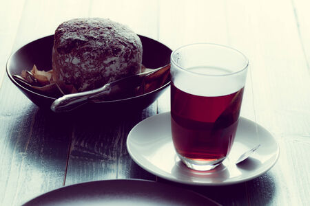 A glas of hot tee and bread on a wooden table.