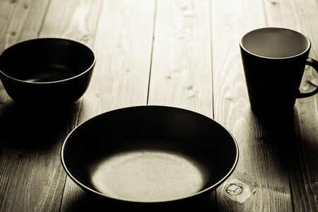 Empty plates on a wooden table. Brown coloured black and white image fine art.
