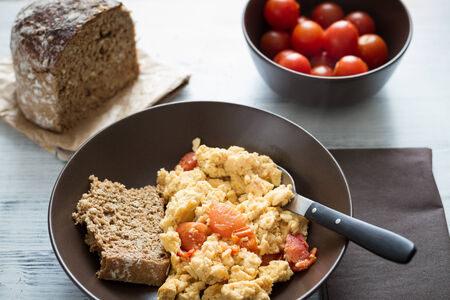 A plate of fresh scrambled eggs  on a white wooden table with healthy tomatoes and fresh bread. photo