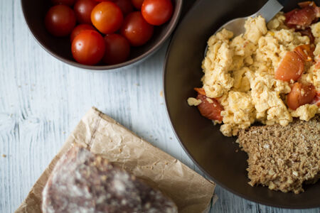 A plate of fresh scrambled eggs  on a white wooden table with healthy tomatoes and fresh bread.