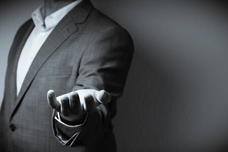 The image displays on individual dressed in a suit holding one hand to the front with a giving gesture. Only the person