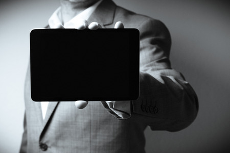 The image displays on individual dressed in a suit holding a tablet computer. Only the person